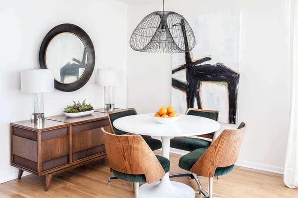 Small dining room with white walls, a round mirror and statement lamps and art