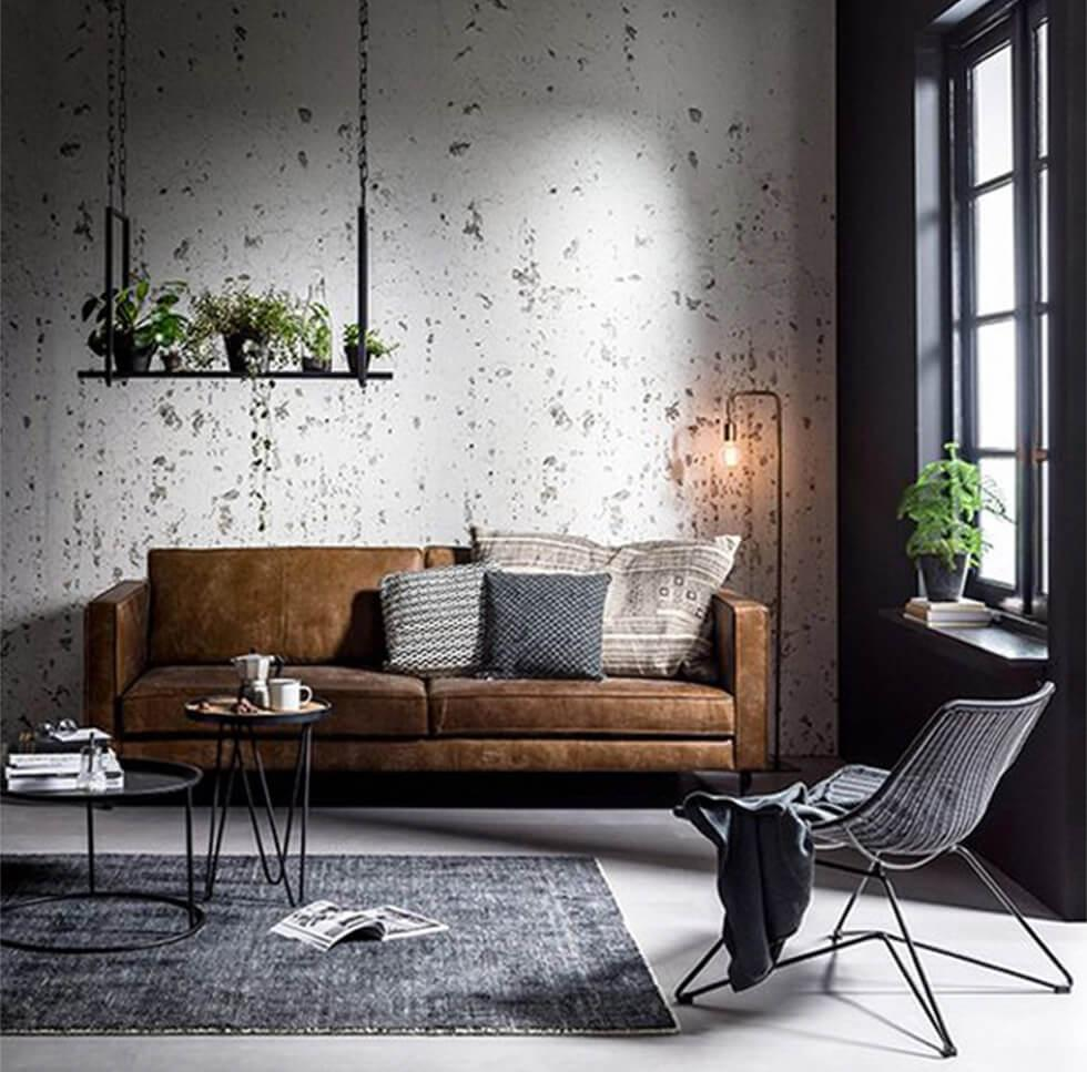 open-plan industrial living room with a brown sofa, bare walls and indoor plants