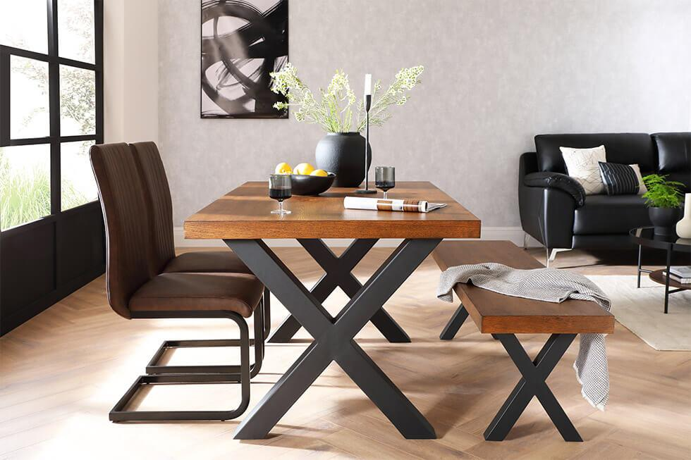 a wood and metal dining set in an open-plan space with a bench and leather chairs