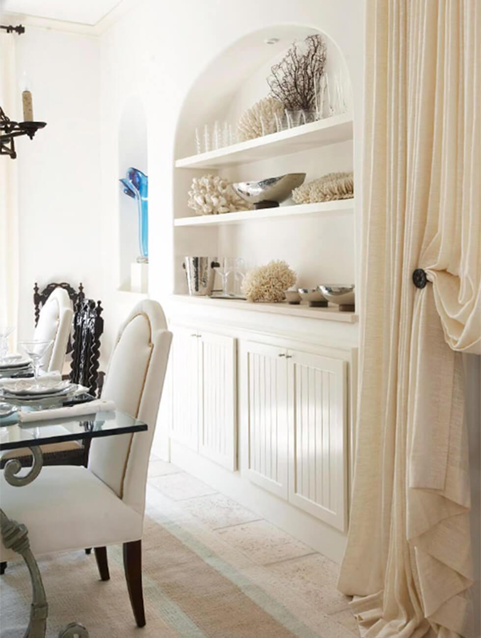 Arched alcove with shelves and cupboards in a neutral white dining room.