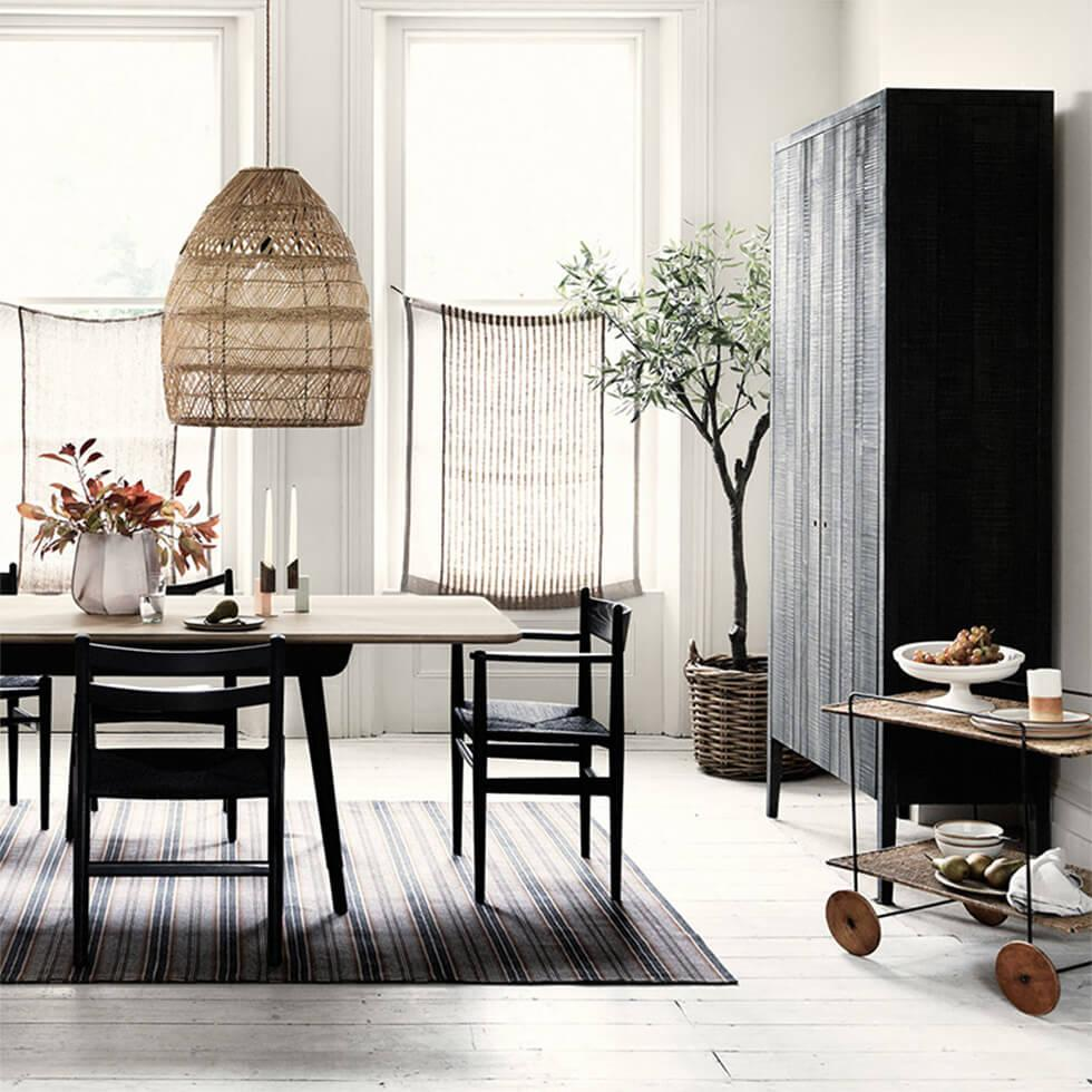 Wooden dining room with woven pendant lamp and large larder cupboard