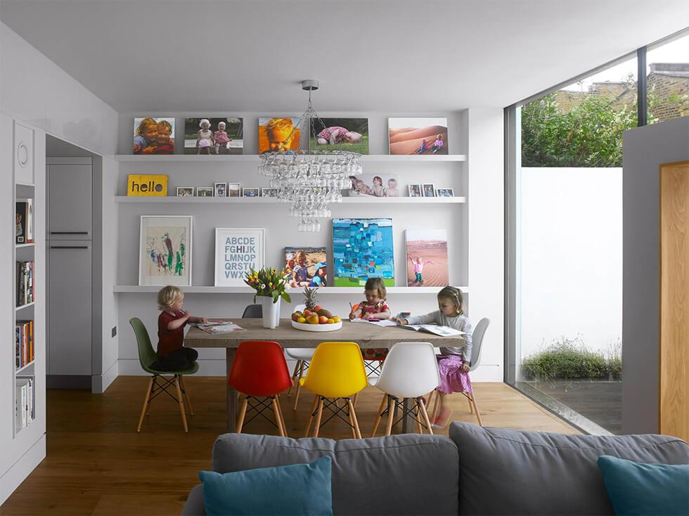 Open plan dining room with colourful chairs and open shelves with art displayed