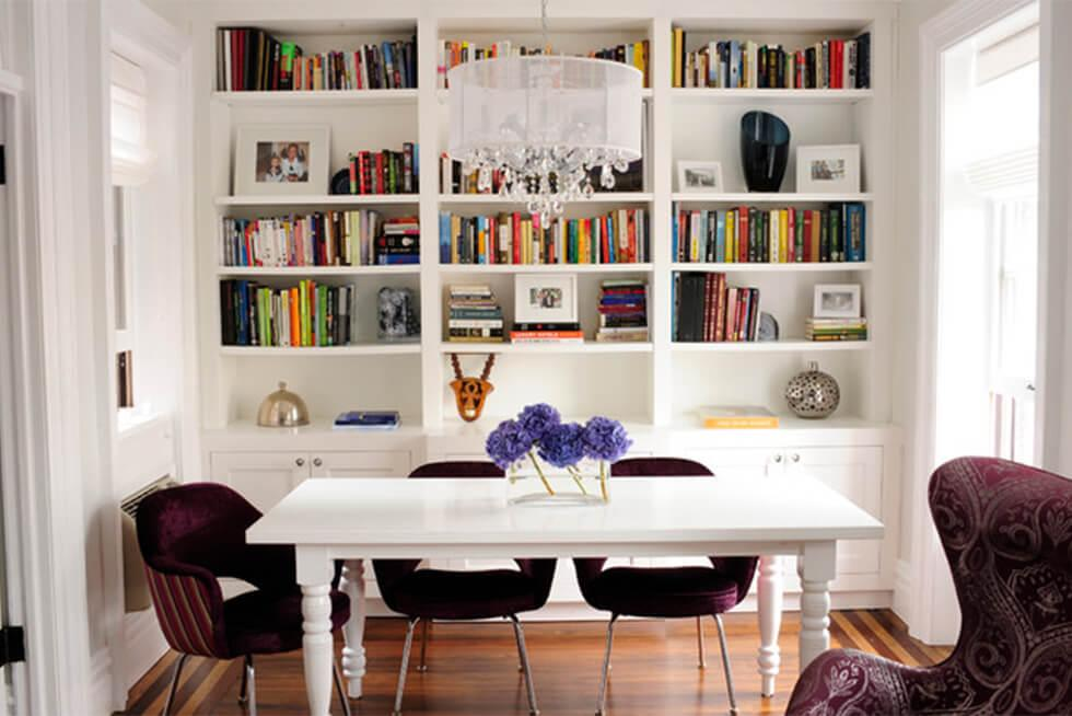 Modern dining room with dark velvet dining chairs, white table, and bookshelves