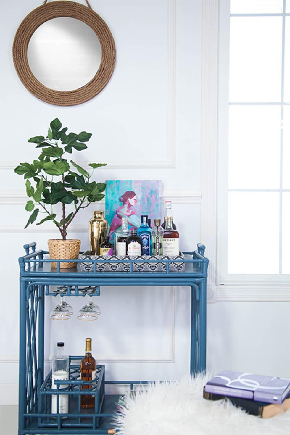 Elegant blue bar cart in a white room with art and plants