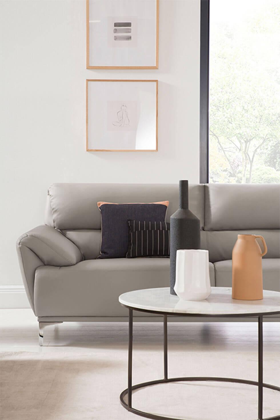 Minimalist living room with white walls, grey sofa and black and terracotta decor