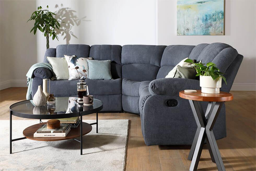 Cosy living room with dark grey fabric recliner sofa, round coffee table and grey rug