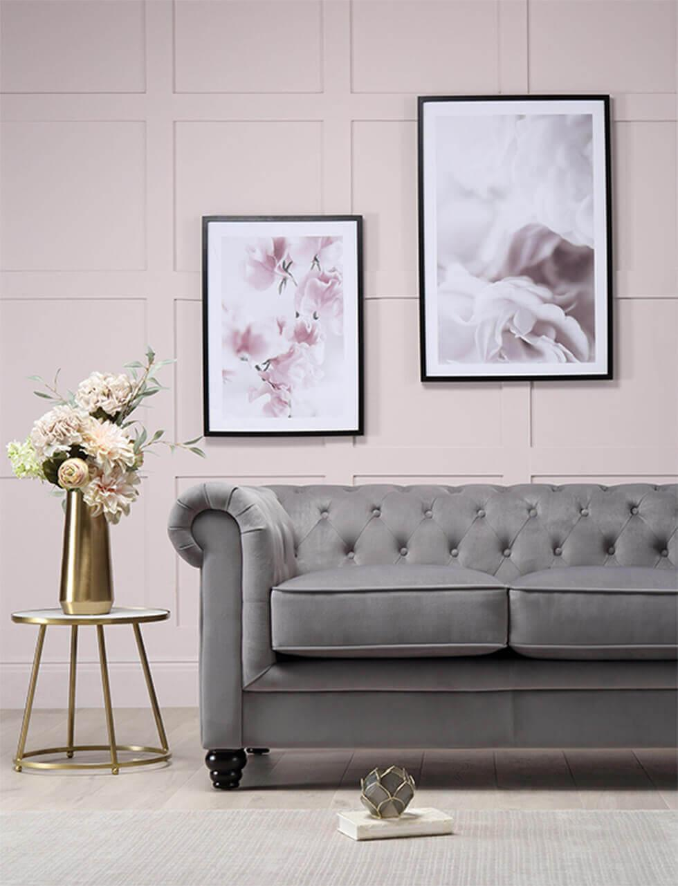 Grey velvet Chesterfield sofa in a muted pink room with a gold vase of flowers
