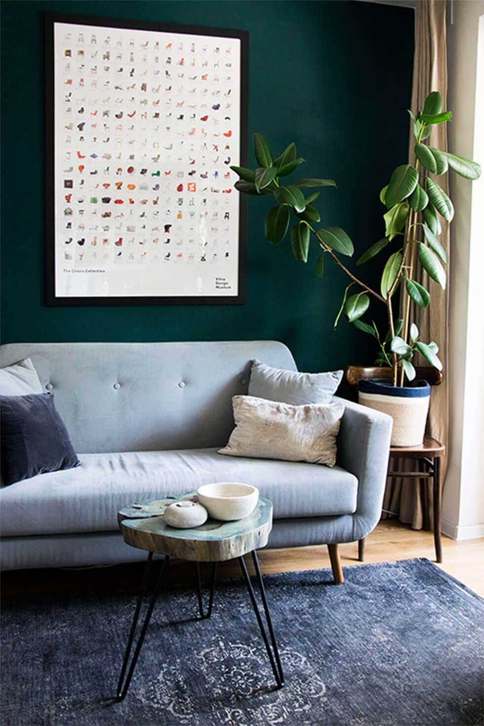 Grey sofa against a dark wall, with a blue rug