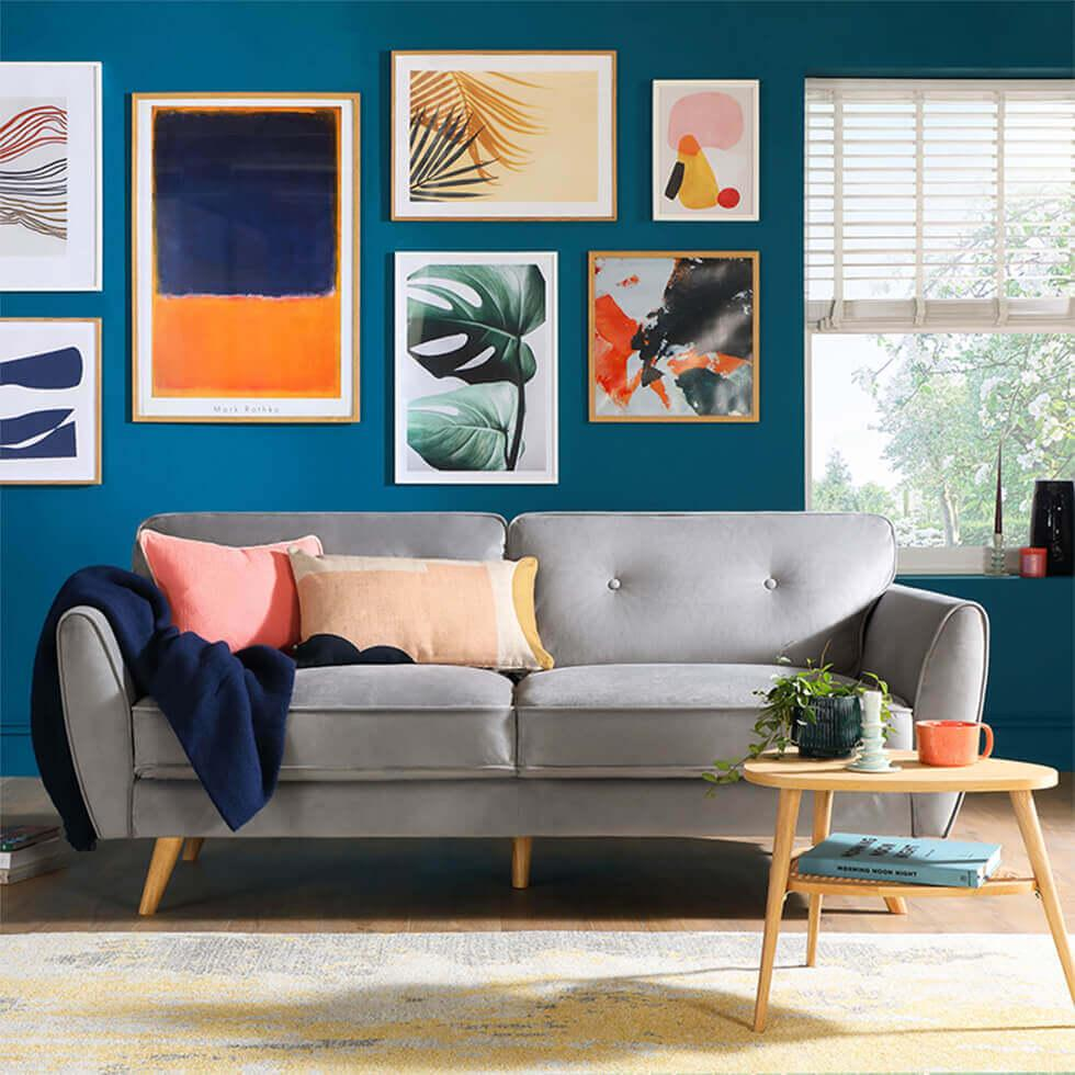 Grey velvet sofa in a teal living room with a colourful gallery wall