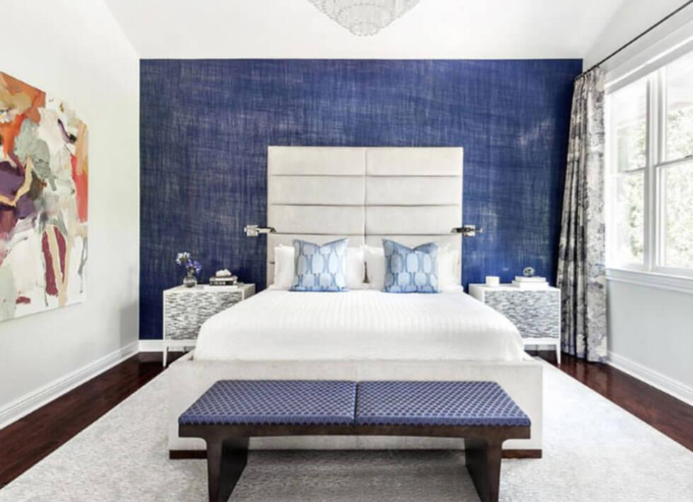 Blue bedroom feature wall with a white bed.