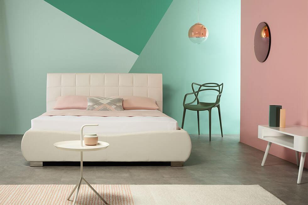 Contrasting colour block bedroom walls in neo-mint green and blush pink.