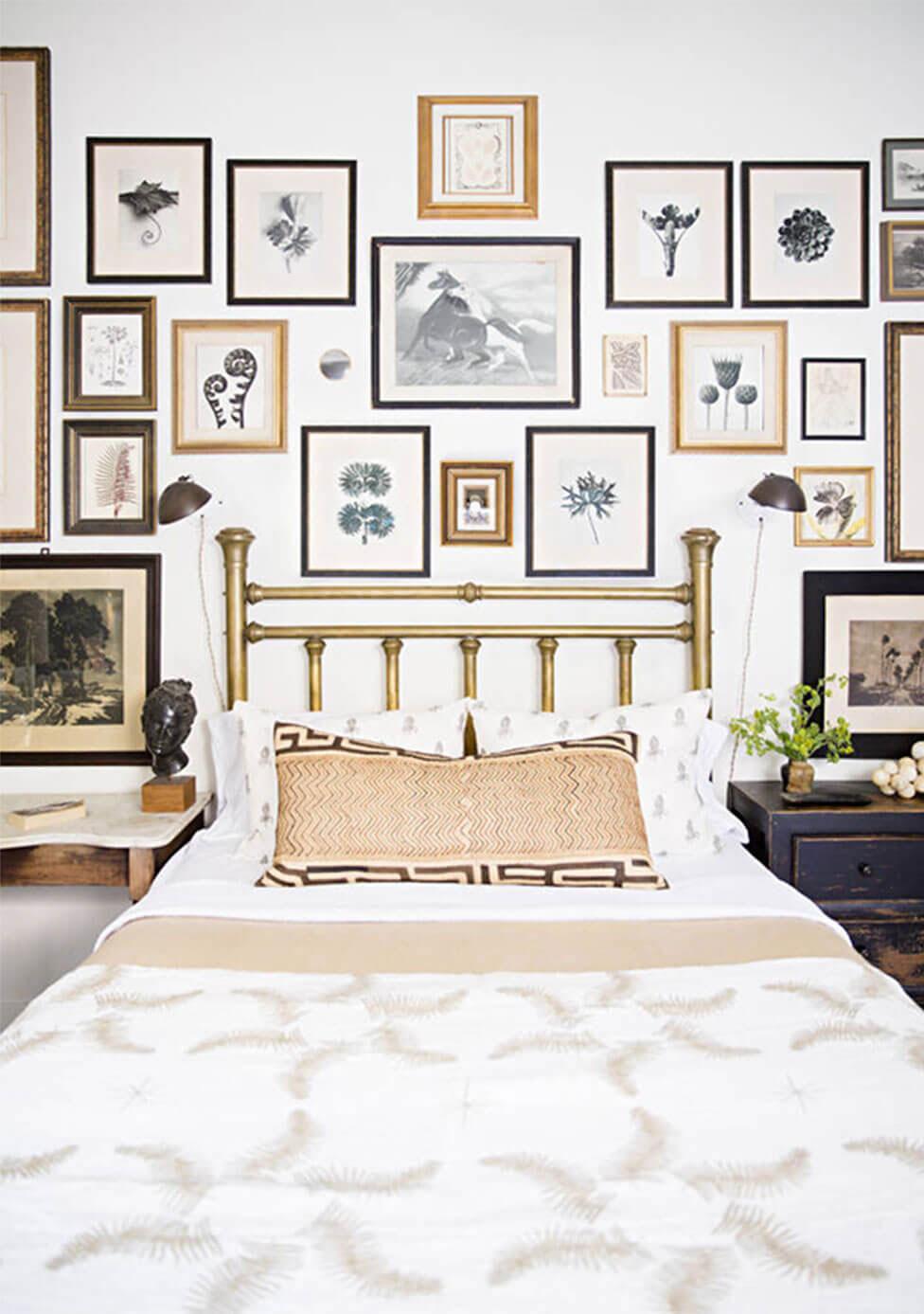 Gallery wall of framed artwork on a bedroom wall.