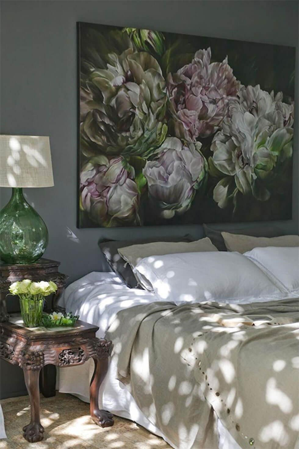 A bedroom wall with large statement artwork framed above the bed.