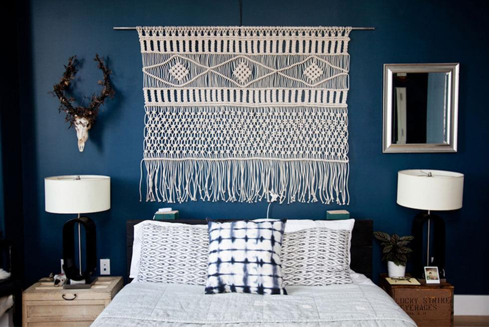 A bohemian style bedroom wall with a knotted macrame hanging.