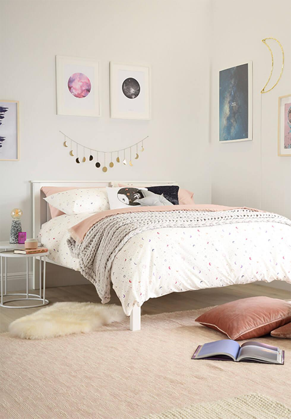 A cosmic space inspired bedroom with metal garlands and art on the walls.