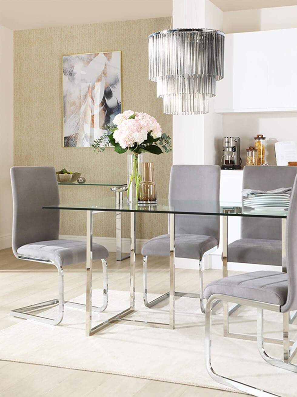Glam chrome and glass dining room with grey velvet chairs and statement chandelier