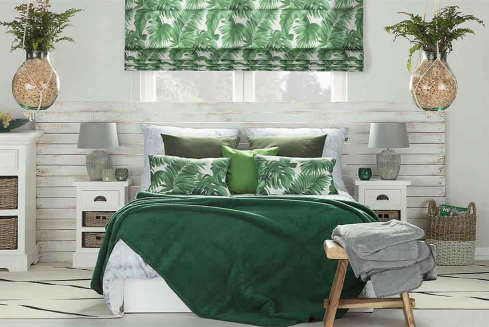 Tropical green bedroom with white wooden headboard and leaf prints.