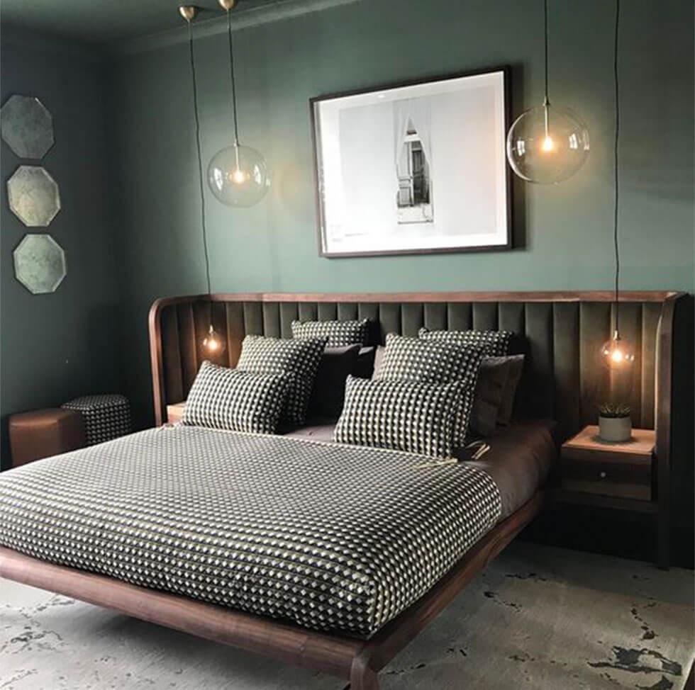Dark olive green bedroom with a cosy velvet headboard.