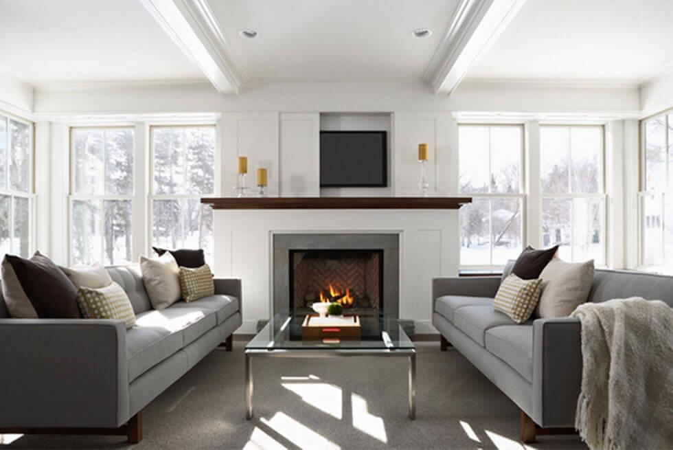 A living room layout where the cosy grey sofas are arranged in symmetrically to create order