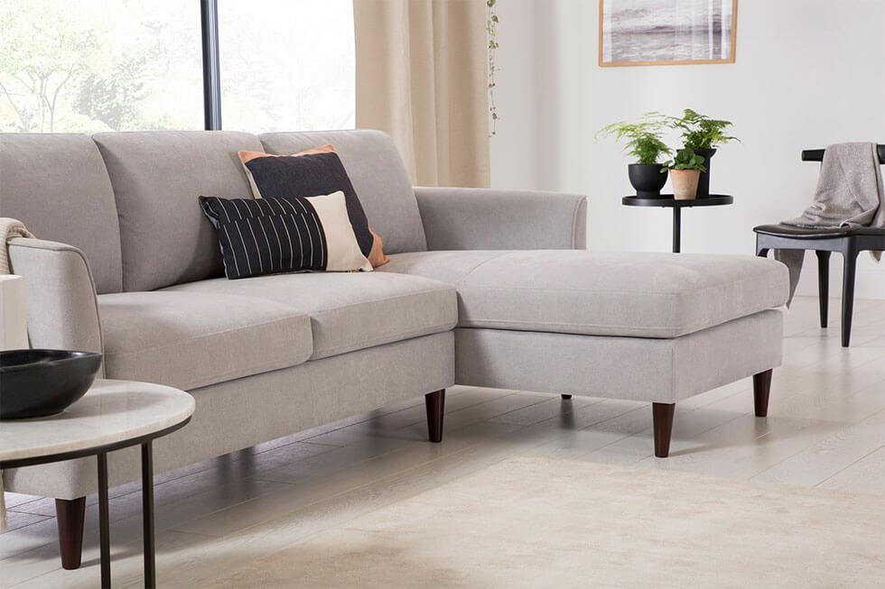 A minimalist living room with a grey corner sofa