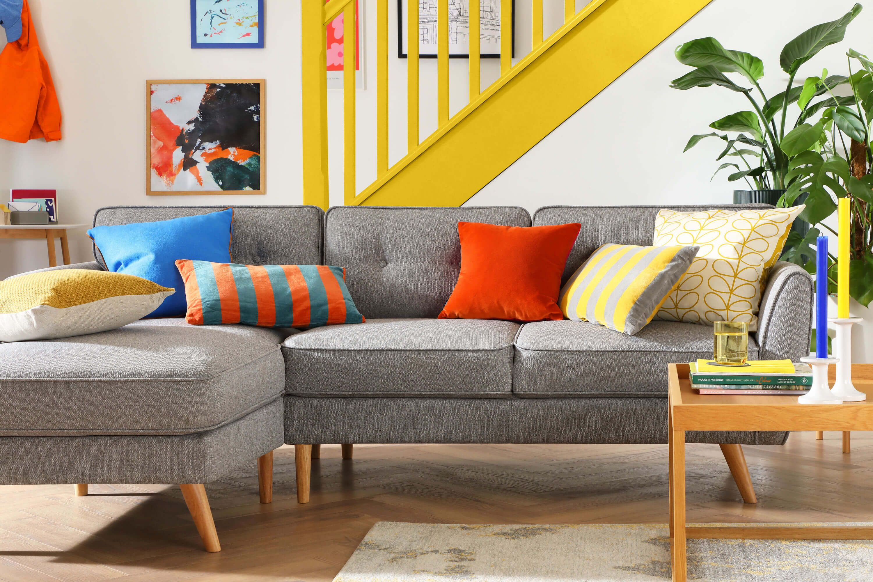 Grey fabric sofa in a bright and modern living room with yellow accents