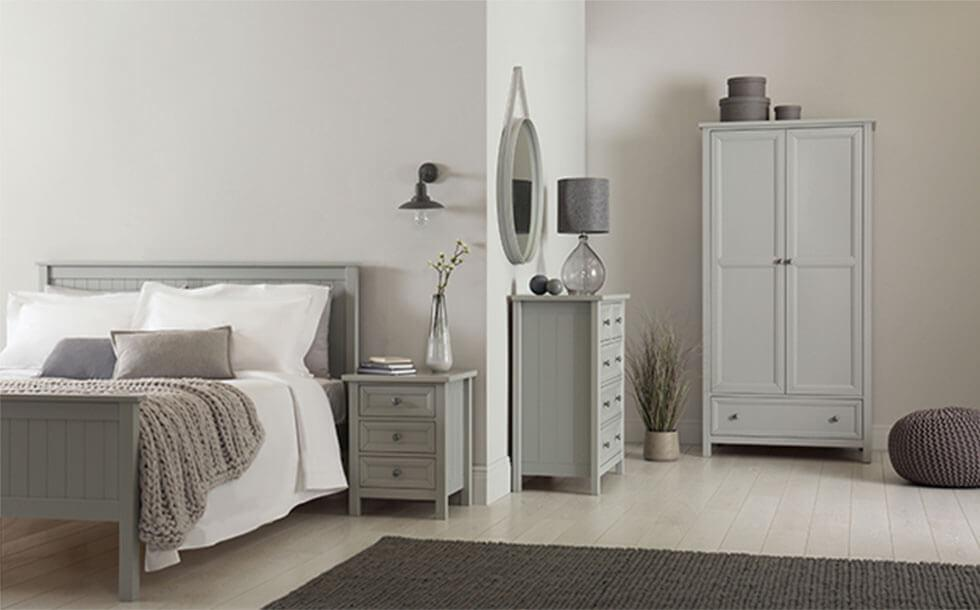 Monochrome grey bedroom with matching cabinets, drawers, and bed frame.