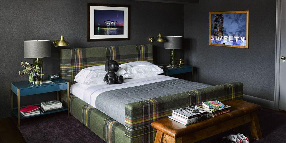 Moody dark grey bedroom with plaid green bed, modern bedside table and framed art.