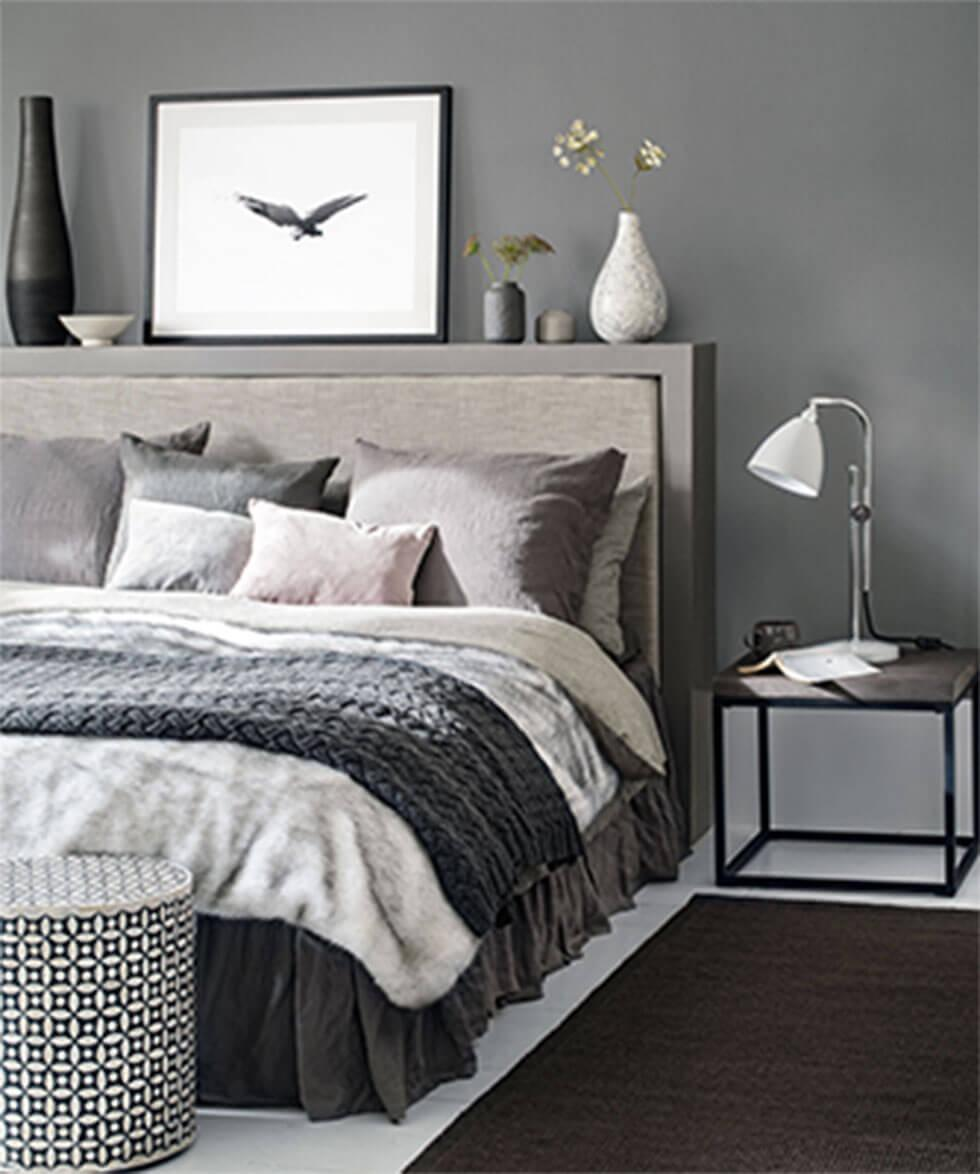 Grey bed layered with pillows, a blanket, and a throw.