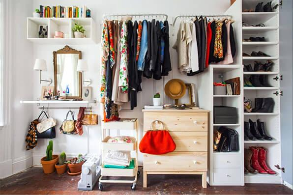 open concept wardrobe with hanging rods, hooks and a small dresser.