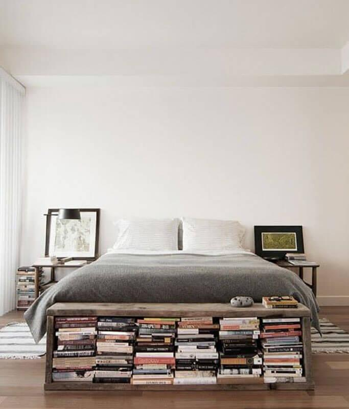 A storage bench at the foot of a bed with lots of books.