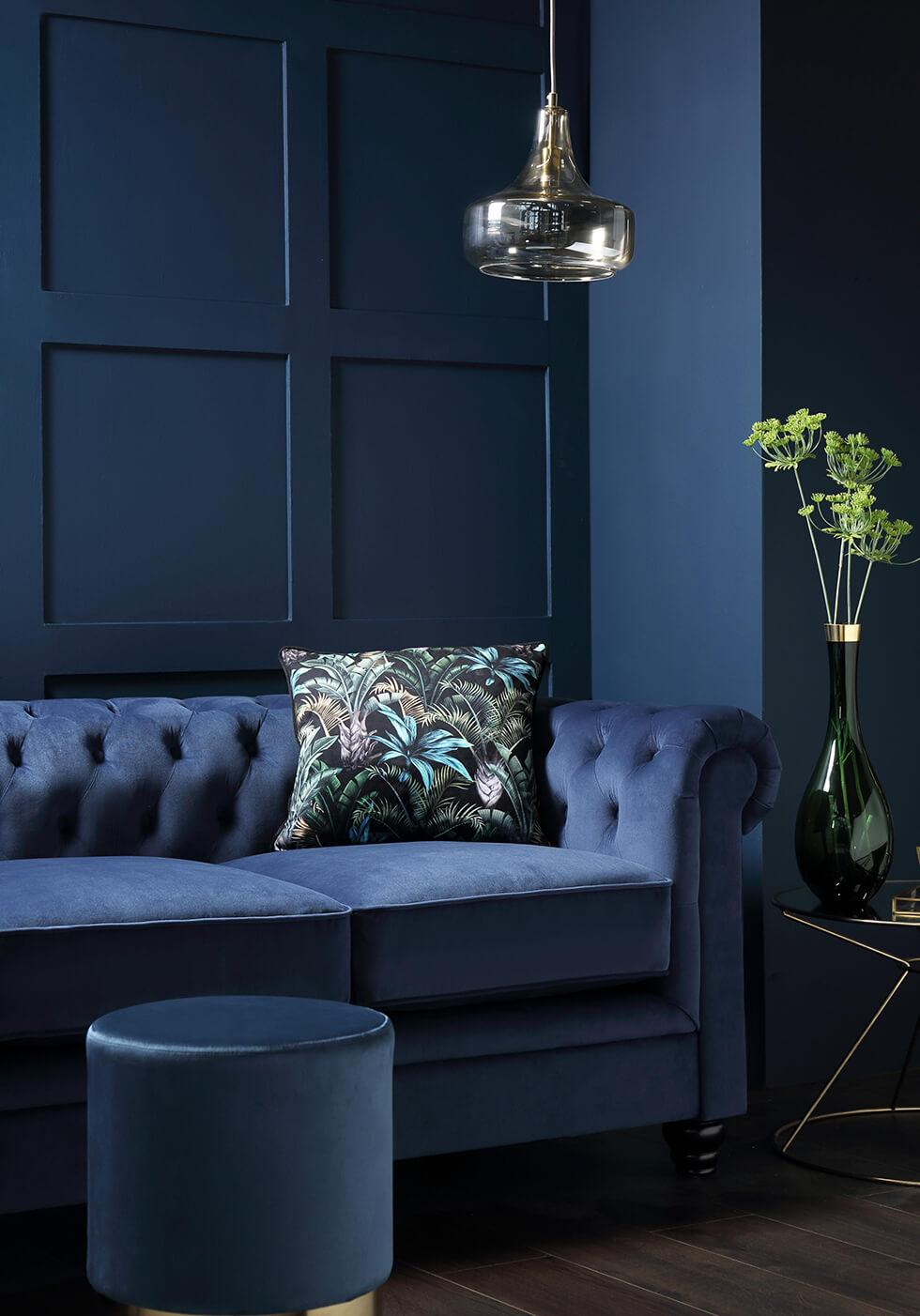 Blue room with blue velvet Chesterfield sofa and leather footstool