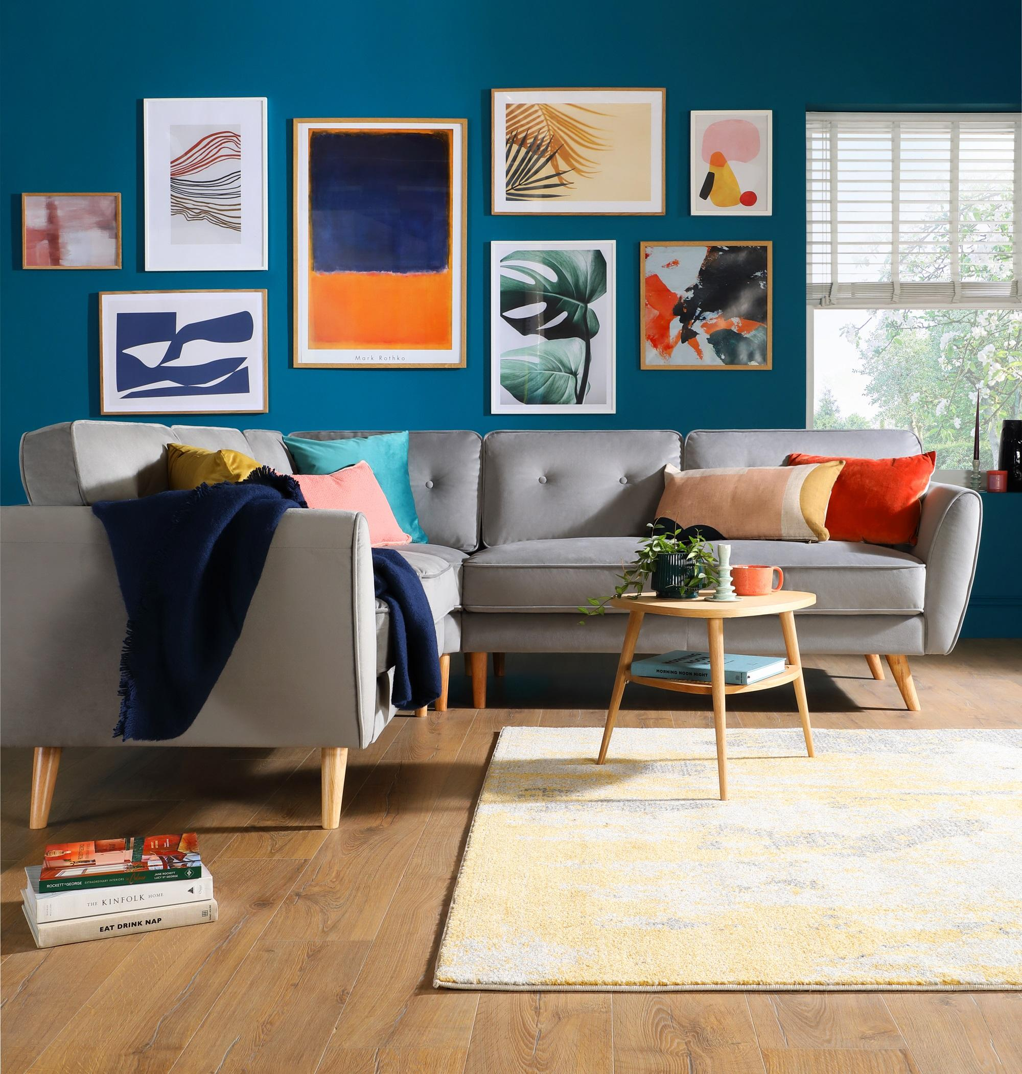 Bright teal gallery wall with grey mid century fabric sofa