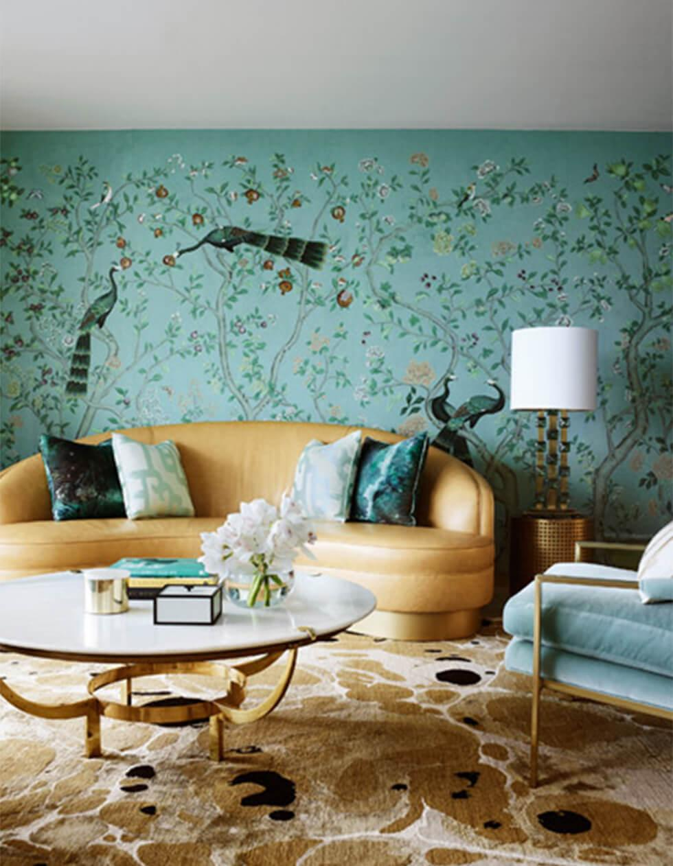 Mid century mint green living room with patterned wallpaper and a light brown couch and rug