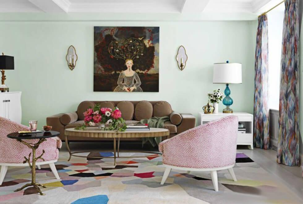 Mid century mint green living room with olive green velvet sofa, pink armchairs and patterned rug