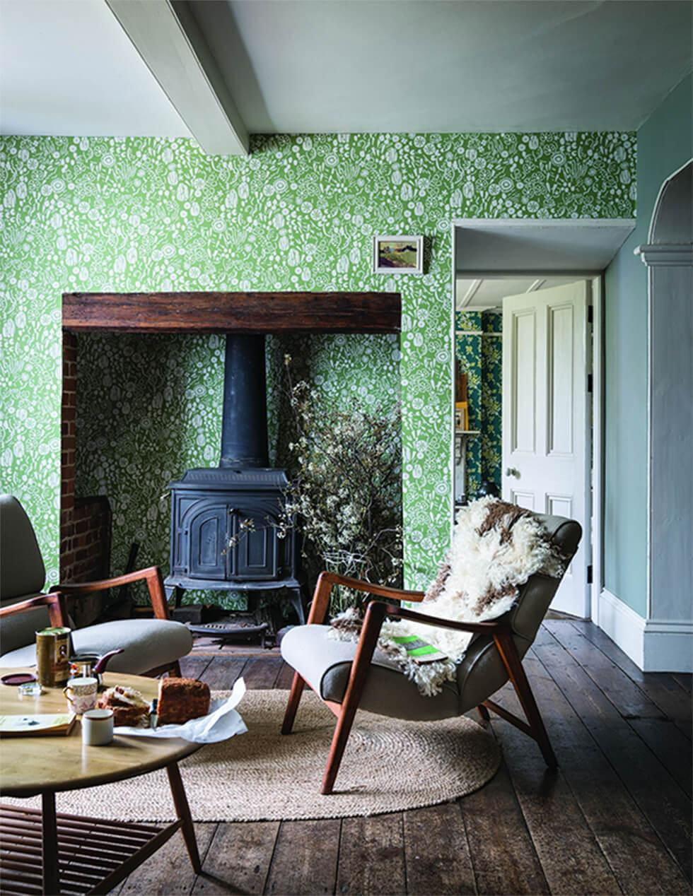 Green country living room with bright printed wallpaper, furnace, and low dark wood armchairs