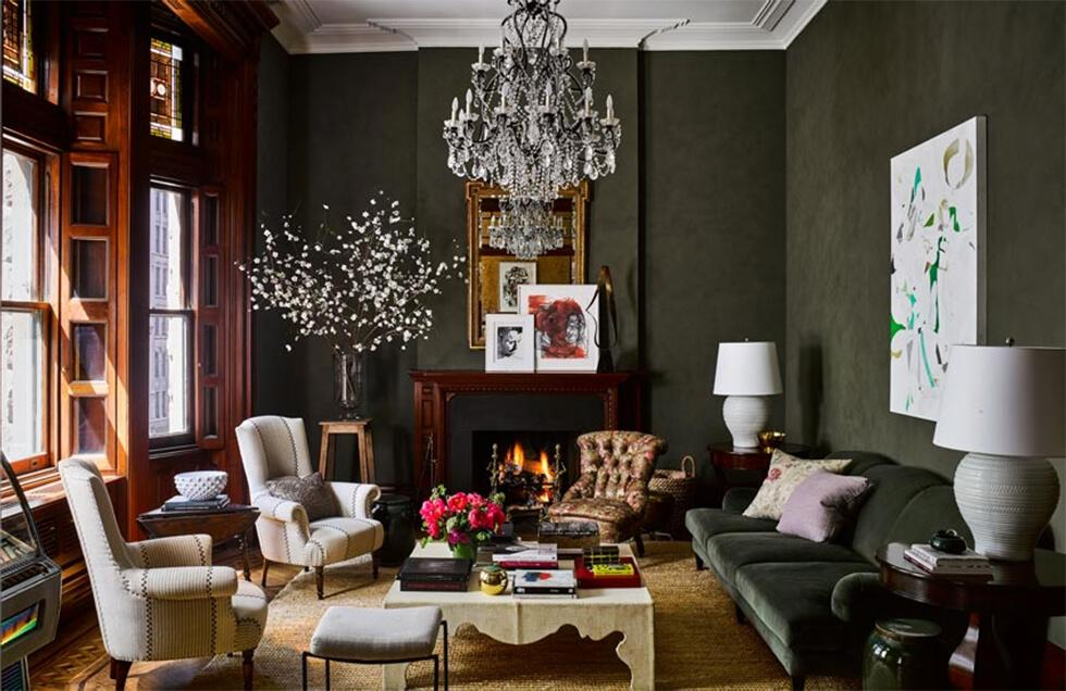 Classic living room with dark khaki walls and sofa, chandelier and white accents