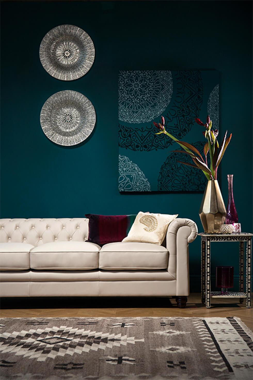Dark teal living room with global decor and classic white leather Chesterfield sofa