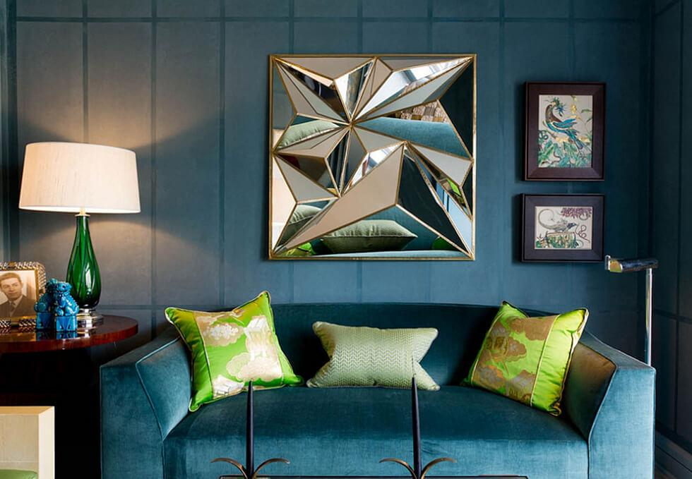 Dark teal living room with matching teal sofa, light green accent cushions and geometric art