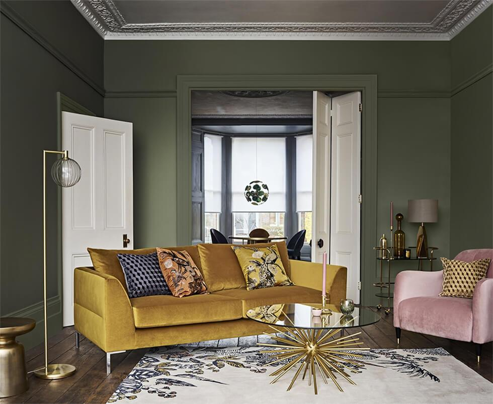Green living room with contrasting mustard velvet sofa and soft pink armchair