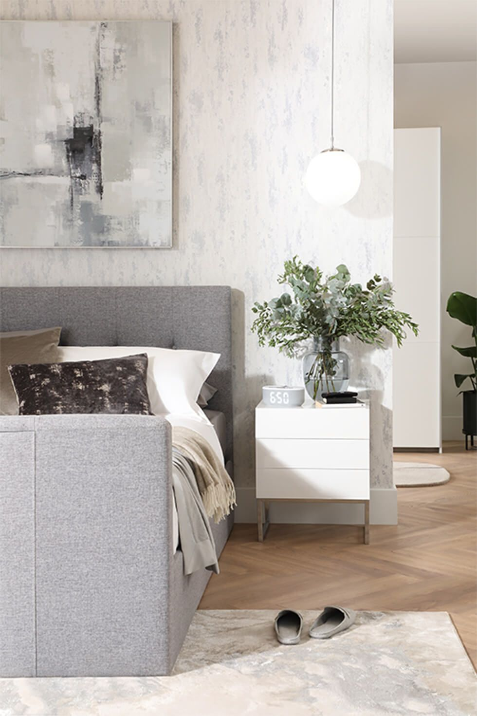 White bedroom featuring a grey fabric bed and a white side table with a vase of plants
