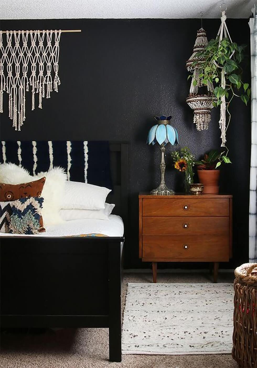 Black and white bedroom in a modern boho style with a black feature wall.