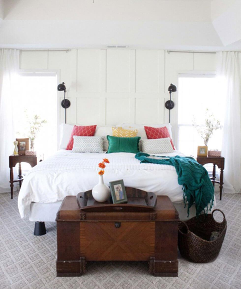 White bedroom with colourful throw pillows and wooden trunk.