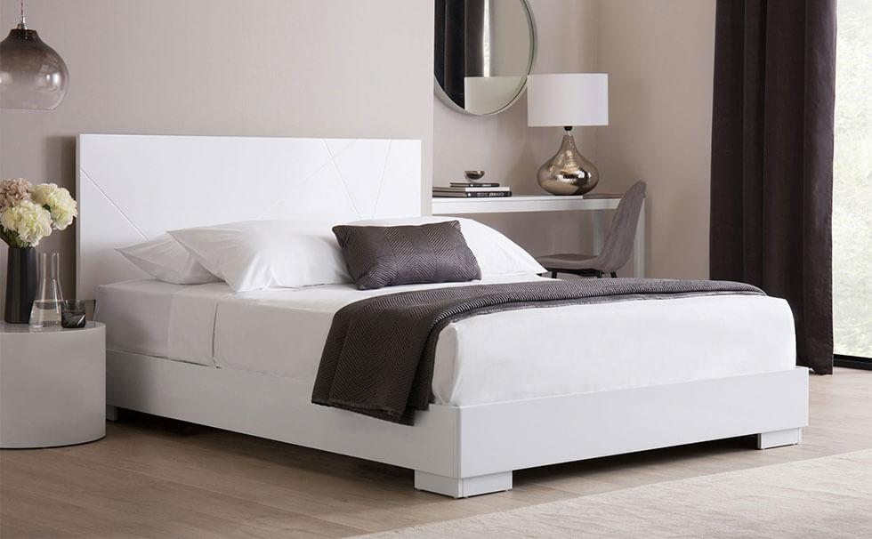 White bedroom with minimalist white high gloss bed.
