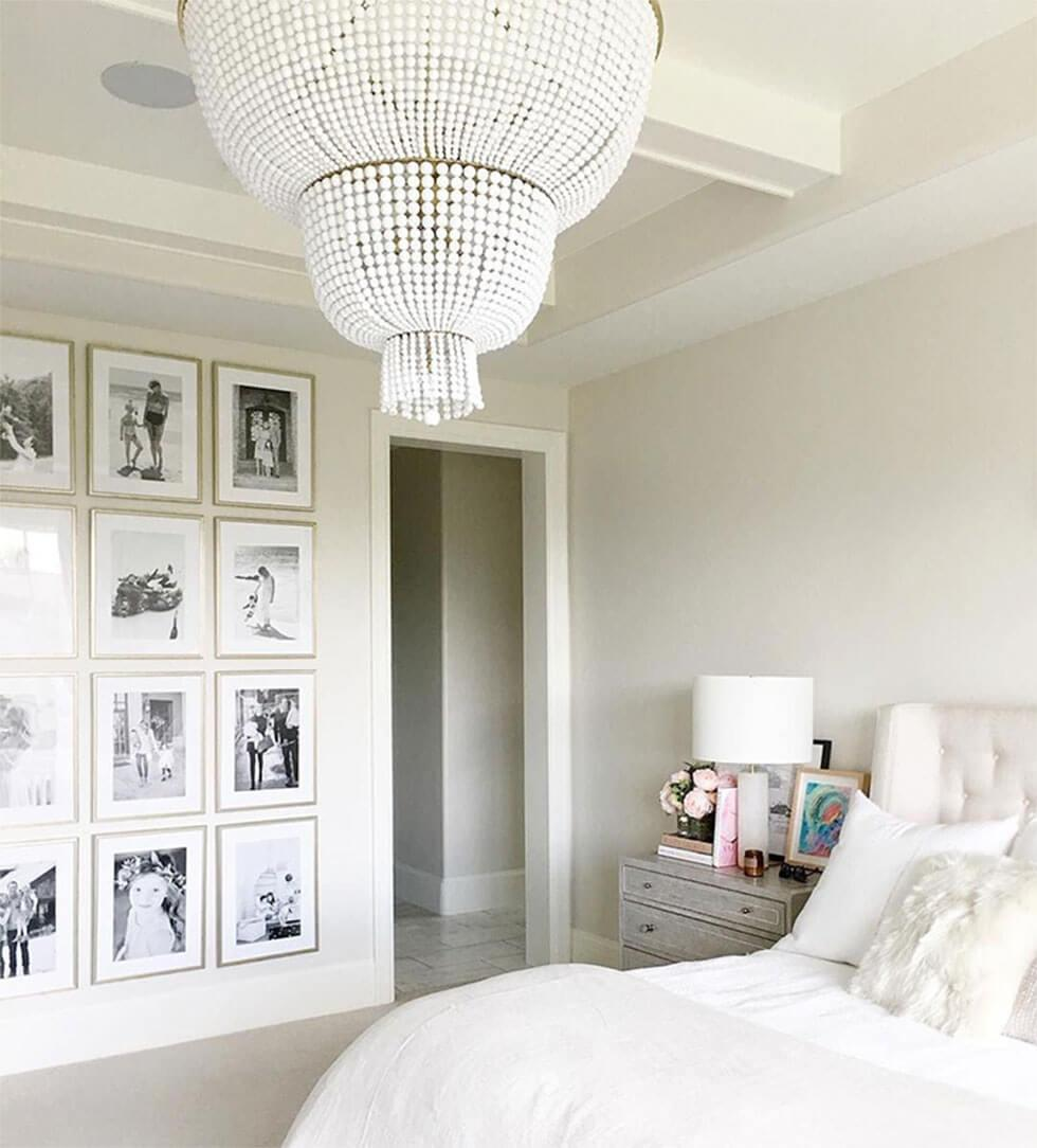 White bedroom with gallery wall of black and white photos.