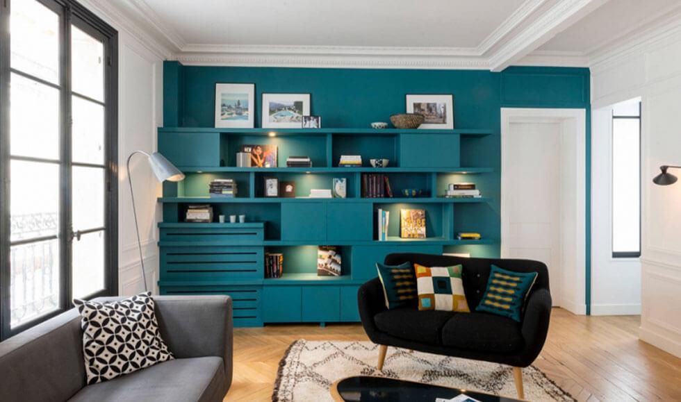 Living room with bold teal bookshelf wall