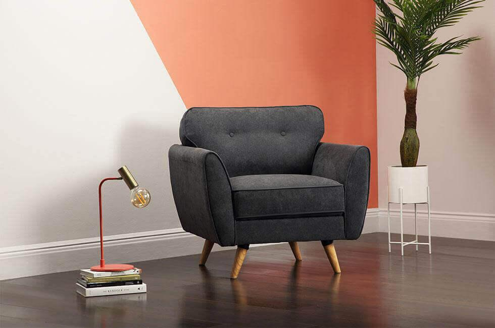 grey armchair in front of a coral geometric colour blocked wall