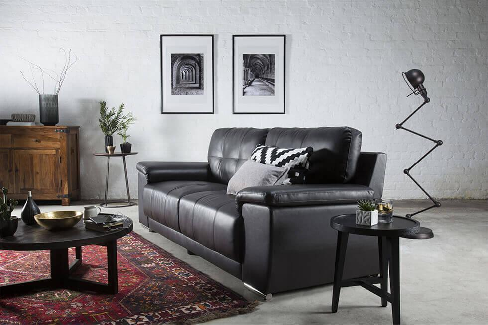 black leather sofa in an industrial style living room with exposed brick wall