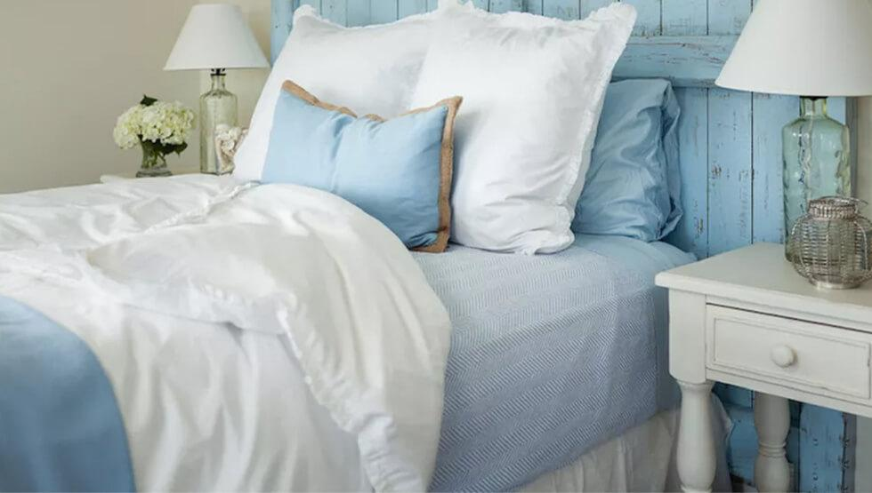 Light blue rustic bedroom with a wooden bed headboard