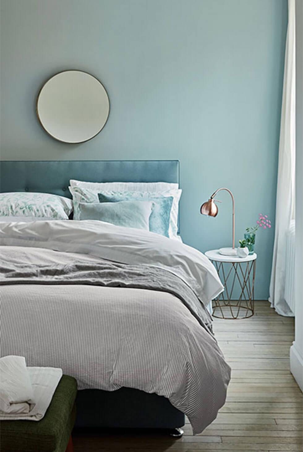Calm, blue modern bedroom in tonal shades and soft bedding