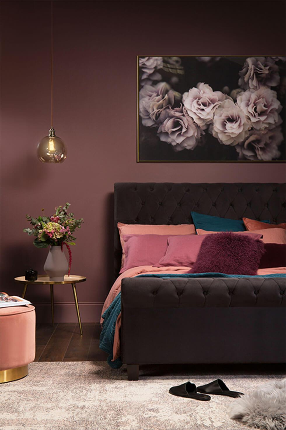 Black velvet bed with pink cushions and stool, with dark purple walls